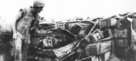 Buffalo marine inspects a collapsed con thien bunker made of dirt filled ammunition boxes